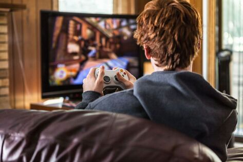 Un jeune homme joue à la console de jeu. Image d'illustration.