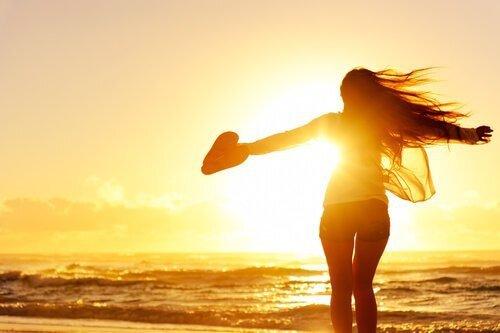 Femme-avec-un-coeur-dans-la-main-coucher-du-soleil-sur-la-plage-500x333