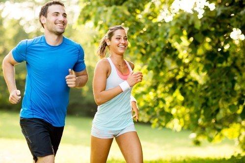Une femme et un homme qui font un jogging l'air heureux