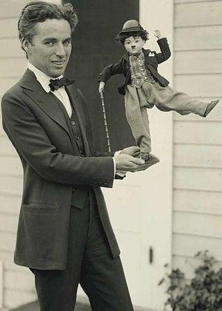 Photographie de Charlie Chaplin debout et en costume tenant une poupée représentant Charlot