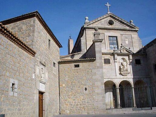 Enceinte de pierre d'un couvent, avec à droite la façade de l'église, de style classique.