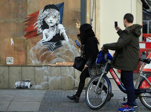 Commuters in London took pictures of a new piece of art by Banksy opposite the French embassy on Monday. The work is critical of the use of tear gas in the refugee camp in Calais.