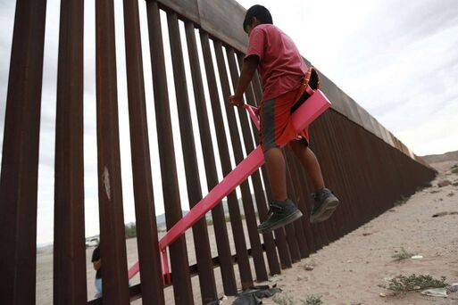 Children playing together on each side of  the Mexican Border ...