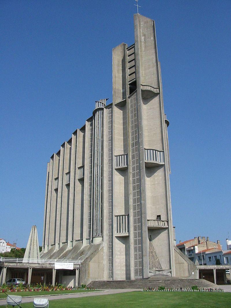 Photographie d'une église moderne en béton brut. Sur trois niveaux, une nef longue et étroite dont les murs côtelés sont ornés de longues bandes verticales faites de carreaux de verre et de balcons aveugles aux striures verticales. Rappelant la forme d'un paquebot se dresse à la «proue» un clocher fait de blocs de béton parallélépipédiques. La base présente des contreforts de béton et un vitrail triangulaire donnant sur un large perron. Un terre-plein couvert de gazon avec des massifs fleuris sépare l'église du parking qui l'entoure.