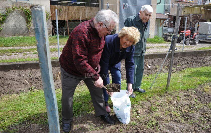 Nicole et Jean Bézard, en train de ramasser de la terre d'Alsace dans le jardin de Marcel. (Photo DNA L. Habersetzer)