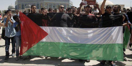 Des Palestiniens brandissant leur drapeau national à lors d'une manifestation