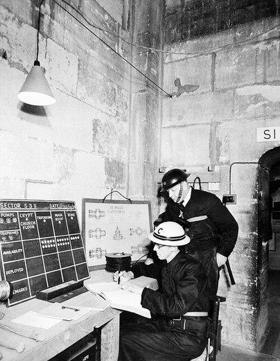 Vers la même époque, dans une salle de contrôle (où l'on distingue, contre le mur, un plan détaillé de la cathédrale) sont coordonnés des guetteurs prêts à parer les éventuels départs d'incendies pouvant toucher le monument pendant les attaques aériennes.